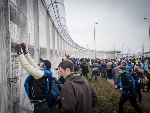 Les manifestants symbolisent leur indignation en accrochant des rubans et messages anti-frontières sur le grillage.
